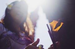 点燃香火棍子的巴厘语妇女 免版税库存图片