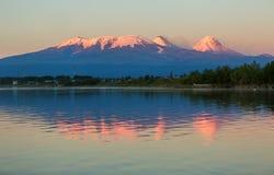 点燃Kluchevskaya小组与反射的火山的日落在河堪察加 图库摄影