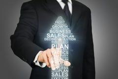 点击在箭头的商人由与生意相关的词形成了 免版税库存照片