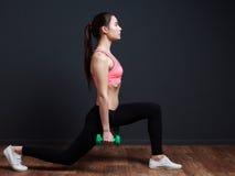 锻炼和健身-做与的亭亭玉立的运动妇女蹲坐我们 免版税图库摄影
