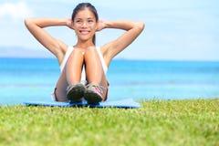 锻炼妇女-仰卧起坐锻炼 库存照片