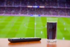 炼焦泡沫腾涌的饮料,在桌上的电视遥控 观看的橄榄球(socce 库存图片