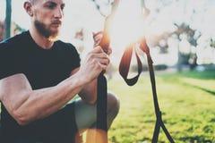 锻炼生活方式概念 肌肉运动员TRX为行使做准备外面在夏天公园 晴朗巨大trx的锻炼 免版税库存图片