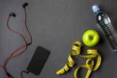 锻炼计划用健身食物和设备在灰色背景,顶视图 库存图片