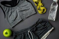 锻炼计划用健身食物和设备在灰色背景,顶视图 图库摄影