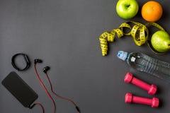 锻炼计划用健身食物和设备在灰色背景,顶视图 免版税图库摄影