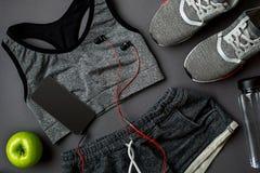 锻炼计划用健身食物和设备在灰色背景,顶视图 免版税库存图片