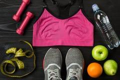 锻炼计划用健身食物和设备在黑暗的背景,顶视图 免版税图库摄影
