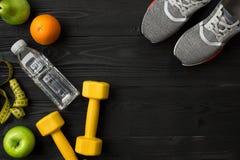 锻炼计划用健身食物和设备在黑暗的背景,顶视图 图库摄影