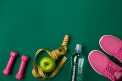 锻炼计划用健身食物和设备在绿色背景,顶视图 库存图片