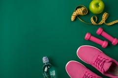 锻炼计划用健身食物和设备在绿色背景,顶视图 免版税库存照片