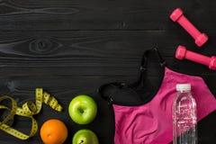 锻炼计划用在黑暗的背景,顶视图的健身设备 库存照片