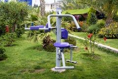 锻炼设备在一个热带庭院里 库存图片