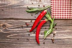 炽热胡椒和迷迭香在土气木背景 免版税图库摄影