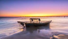 烂掉在美丽的海滩的紫色暮色天空下的小船 免版税库存图片