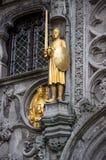 烈士雕塑在圣洁血液的大教堂墙壁上的  比利时布鲁基大厦门开花老红色城镇视窗 库存照片