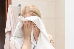 烘干和清洗她的面孔的妇女与一块白色毛巾 免版税库存照片