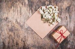 烘干在一个信封和一个小盒子的白花有礼物的 背景和模板 免版税库存图片