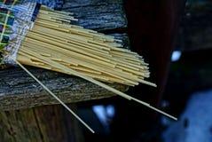 烘干在一个包裹的长的细面条在一张木桌上 免版税库存照片