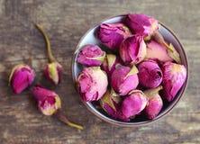 烘干在一个碗的玫瑰色芽花在老木桌上 健康草本饮料概念 芳香疗法茶的亚洲成份 免版税库存图片
