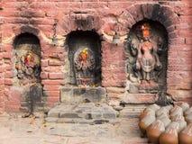 烘干在与老被雕刻的印度神的三个适当位置旁边的泥罐 免版税库存照片