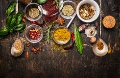 烘干在匙子和碗的五颜六色的香料有在黑暗的土气木背景,顶视图的新调味料的 免版税库存图片