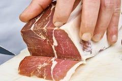 烘干在厨师手切片熏火腿意大利人熟食的被治疗的火腿薄片特写镜头 库存照片