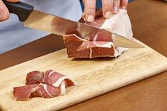 烘干在厨师手切片熏火腿意大利人熟食的被治疗的火腿薄片特写镜头 免版税库存照片