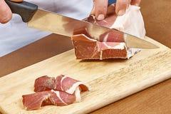 烘干在厨师手切片熏火腿意大利人熟食的被治疗的火腿薄片特写镜头 免版税库存图片