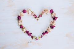 烘干在心脏形状的玫瑰色花在老木背景 图库摄影
