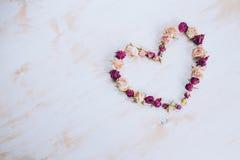 烘干在心脏形状的玫瑰色花在老木背景 免版税库存图片