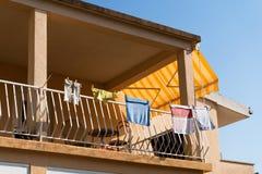 烘干在有天空蔚蓝的阳台的五颜六色的洗衣店在背景 免版税库存照片