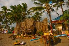 烘干在海滩在棕榈树中,房子的一条绳索的五颜六色的衣裳 Pandan,班乃岛,菲律宾 免版税库存图片