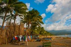 烘干在海滩的一条绳索的五颜六色的衣裳在棕榈树中 Pandan,班乃岛,菲律宾 图库摄影