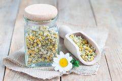 烘干在瓶子和瓢的草本甘菊茶有在背景的新鲜的春黄菊花的,水平 库存图片