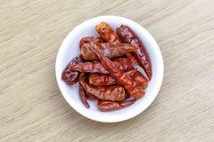 烘干在白色碗的红色辣椒在木桌上 图库摄影