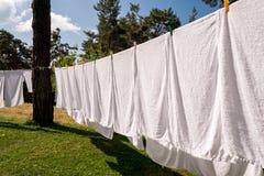 烘干在洗涤的线的新鲜的干净的白色毛巾 免版税库存照片