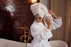 烘干她的有毛巾的浴巾的美丽的女孩头发 在浴以后的女孩 库存图片