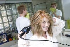 烘干她的头发的妇女在卫生间里 免版税库存图片