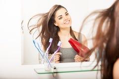 烘干她的头发的逗人喜爱的西班牙妇女 免版税库存照片