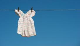 烘干手工编织的线路的婴孩礼服 免版税图库摄影
