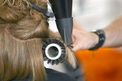 烘干有一把刷子的头发在沙龙 库存图片