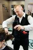 烘干有吹风器和圆的刷子的美发师长的黑色头发 免版税库存图片