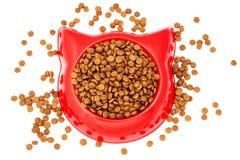 烘干猫的棕色宠物食品在红色塑料碗 图库摄影
