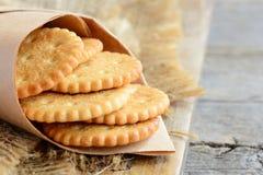烘干稀薄的薄脆饼干在一张包装纸和在麻袋布 背景老木 鲜美酥脆薄脆饼干曲奇饼想法 库存照片