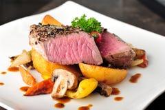 水多的牛排用被烘烤的土豆和蘑菇 免版税库存照片