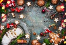 烘烤与自创姜饼人,曲奇饼的圣诞节甜食物框架, stollen用香料、冷杉分支和红色假日deco 库存图片