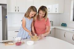 烘烤可爱的白肤金发的30s的妇女在家烹调和愉快与甜可爱的微型厨师小女孩现代厨房一起 库存照片