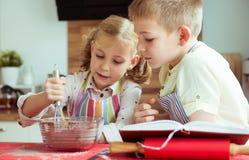 烘烤圣诞节曲奇饼的两个愉快的孩子在厨房 免版税库存照片
