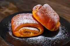 烘烤在一个黑色的盘子 甜小圆面包用糖粉 库存照片